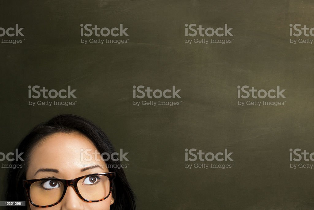 Woman with glasses in front of empty blackboard. royalty-free stock photo