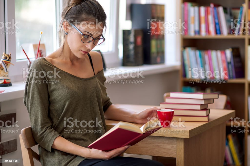 Woman with glasses reading a book with a cup of coffee royalty-free stock photo