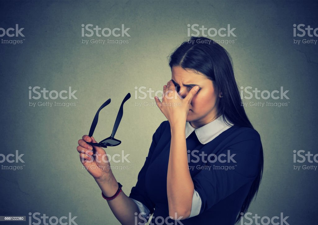Woman with glasses rubbing her eyes feels tired stock photo