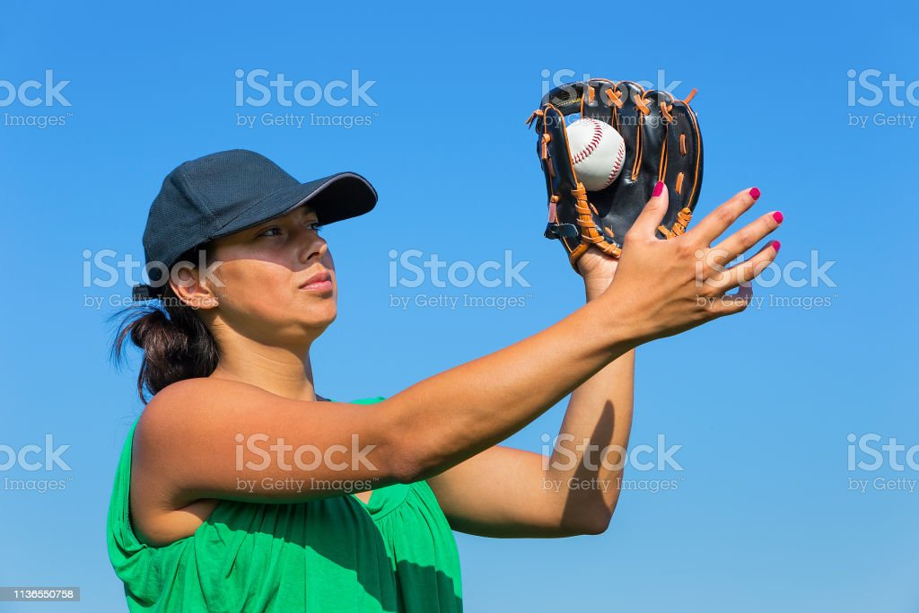 Colombian woman with glove and cap catching baseball outdoors with...