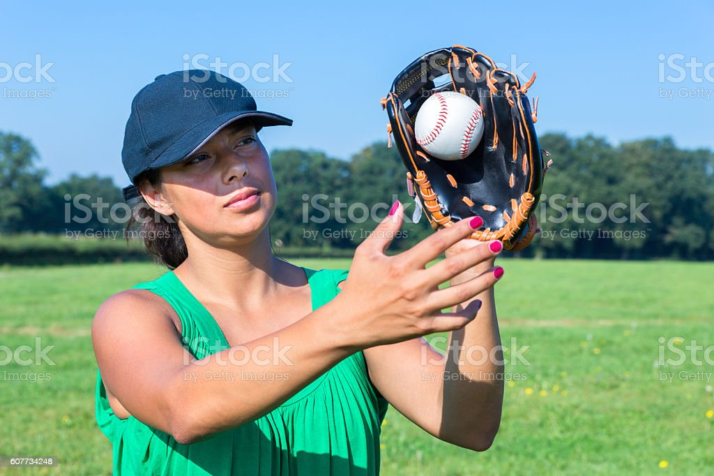 Woman with glove and cap catching baseball outdoors. Young european...
