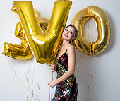 woman with golden balloons on her thirty years birthday