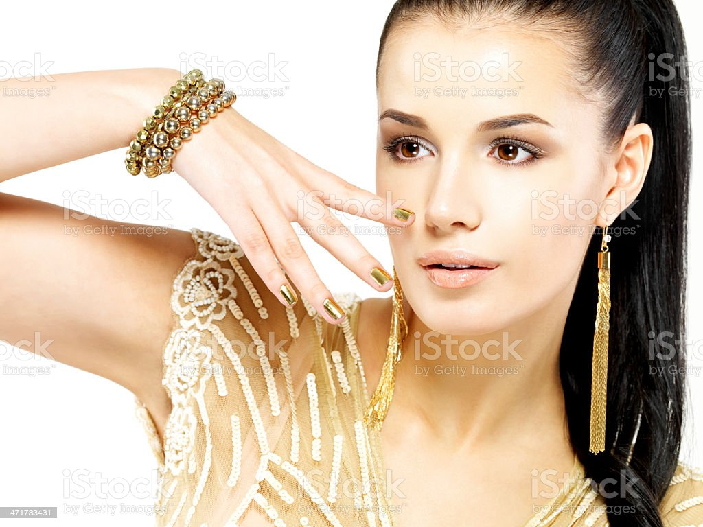 Woman with golden nails and beautiful gold jewelry royalty-free stock photo