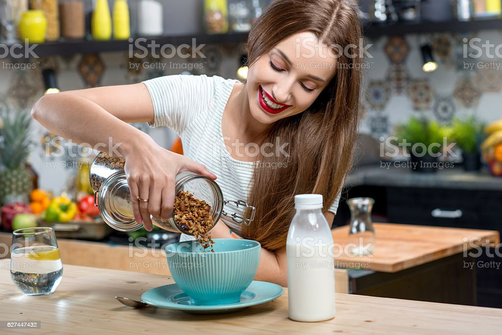 Woman with granola breakfast in the kitchen stock photo