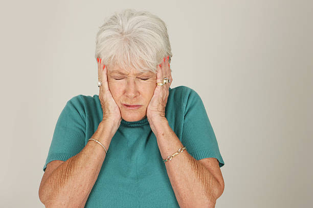 woman with gray hair grimacing with her hands over her ears - covering ears stock photos and pictures