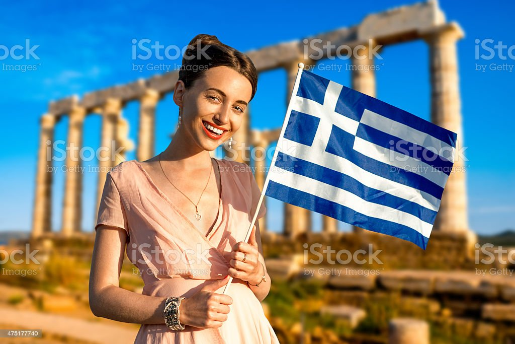 Woman with Greek flag on ancient ruins background stock photo