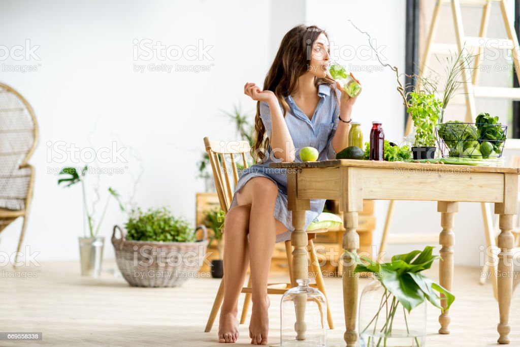 Woman with green healthy food at home stock photo