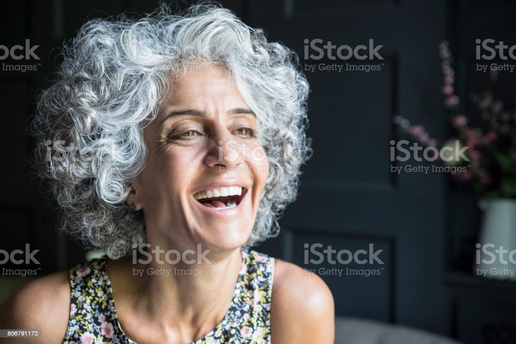 Woman with grey curly hair looking away and laughing stock photo