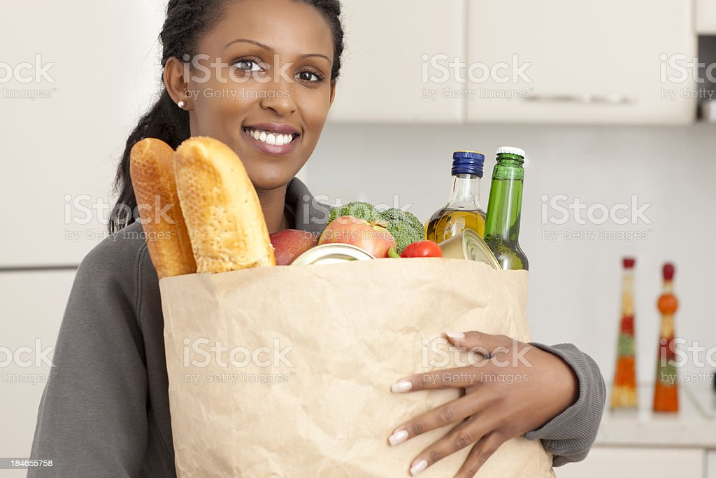 Woman with grocery shopping in the kitchen. royalty-free stock photo