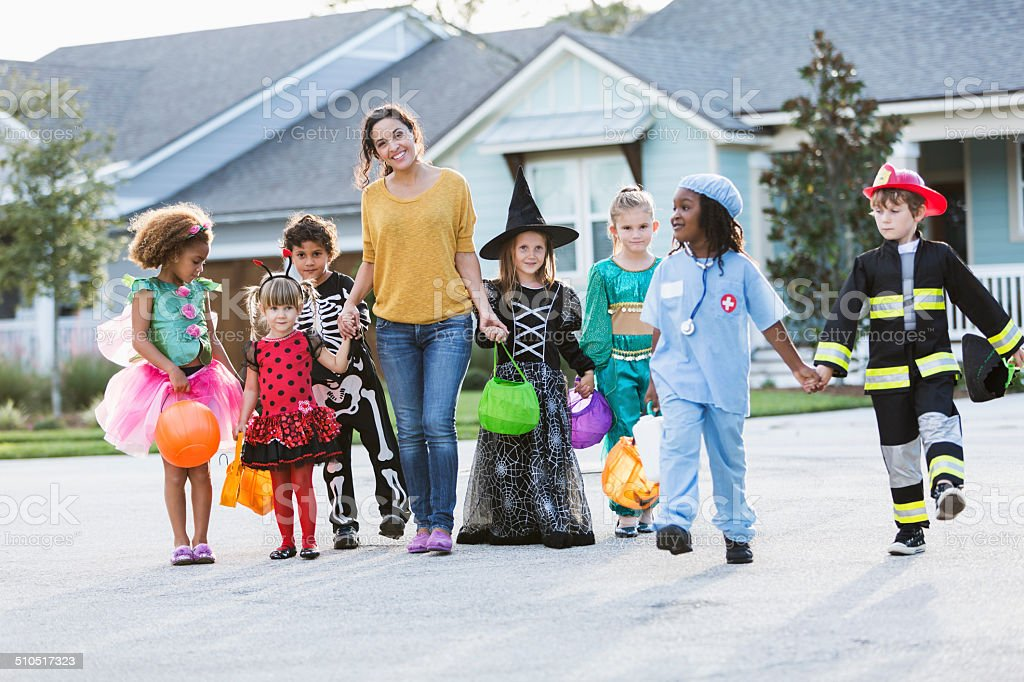 Woman with group of children in halloween costumes stock photo