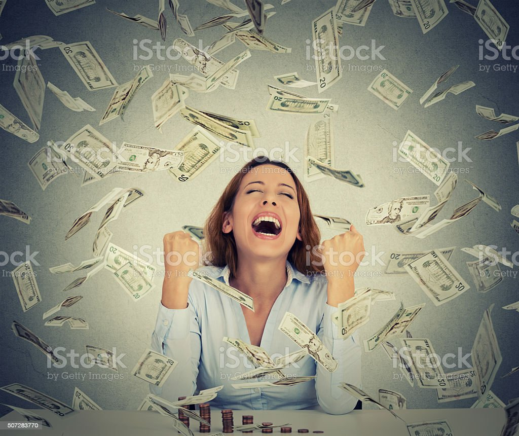 woman with growing stack of coins under money rain stock photo