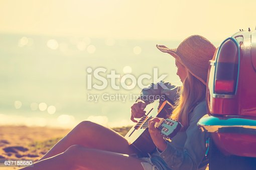 istock Woman with guitar leaning on a car. 637188680