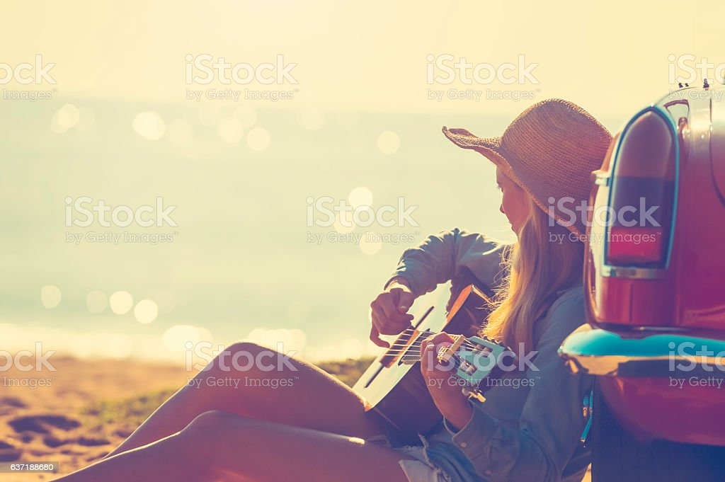 Woman with guitar leaning on a car. stock photo