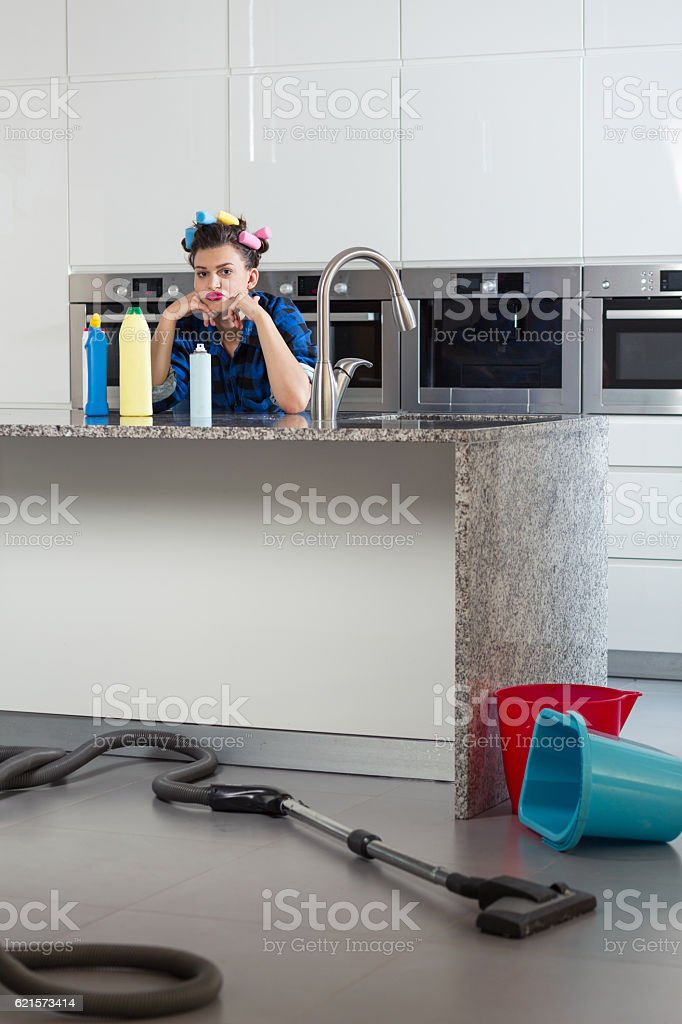 Woman with hair rollers sitting bored in a beautiful kitchen photo libre de droits