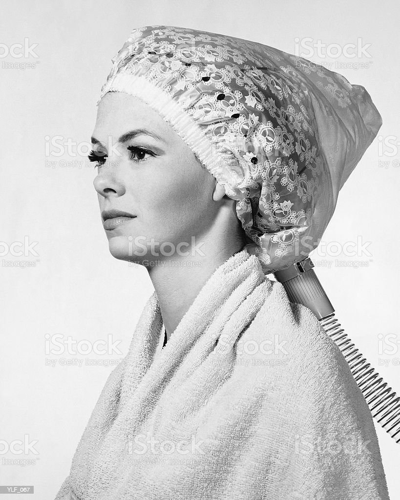 Mulher com secador de cabelo na cabeça foto royalty-free