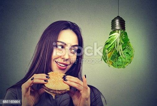 istock Woman with hamburger thinking of alternative diet choices 685165664