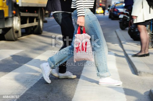 Stockholm, Sweden - April 27, 2011: Two Women crossing street on zebra crossing in central Stockholm Hotorget. One carrying H&M bag. Mid day early spring.
