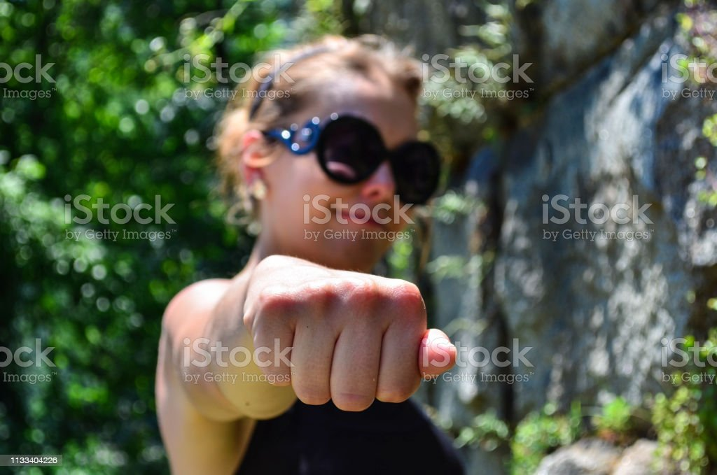 Woman with hand in a knuckle fist position. Smug smile, defocused....
