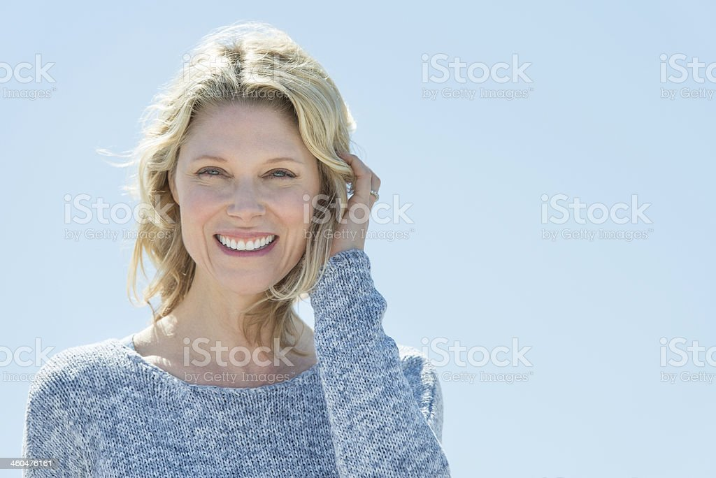 Woman With Hand In Hair Against Clear Sky stock photo