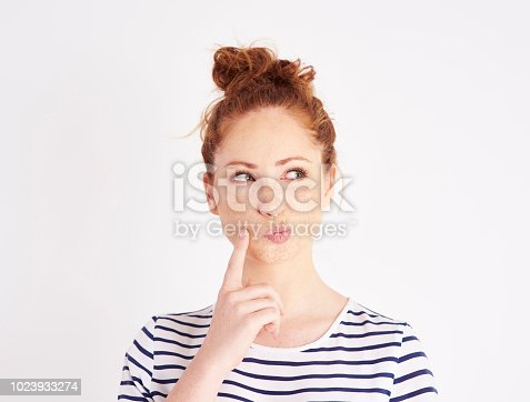 Woman with hand on chin thinking at studio shot