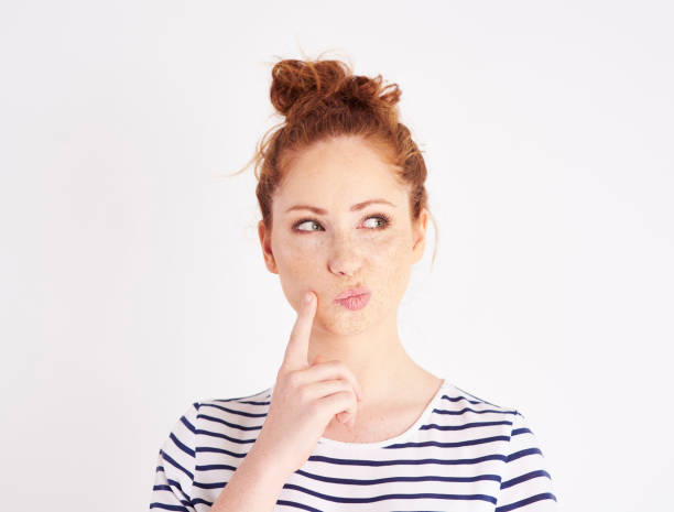 Woman with hand on chin thinking at studio shot Woman with hand on chin thinking at studio shot ambiguity stock pictures, royalty-free photos & images