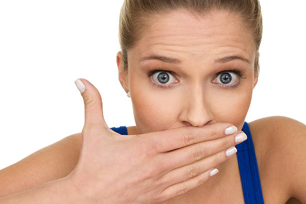 Woman with hand over mouth and surprised expression stock photo