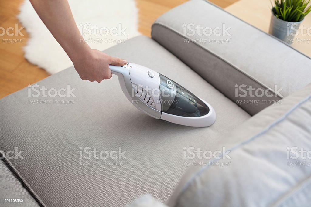 Woman with handheld vacuum cleaning on sofa photo libre de droits