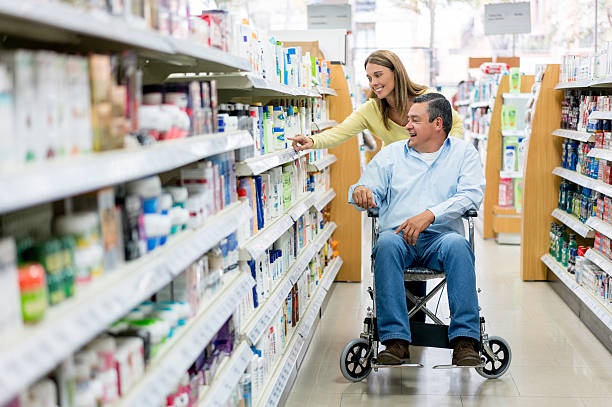 woman with handicapped patient shopping at the pharmacy - lieblingsrezepte stock-fotos und bilder