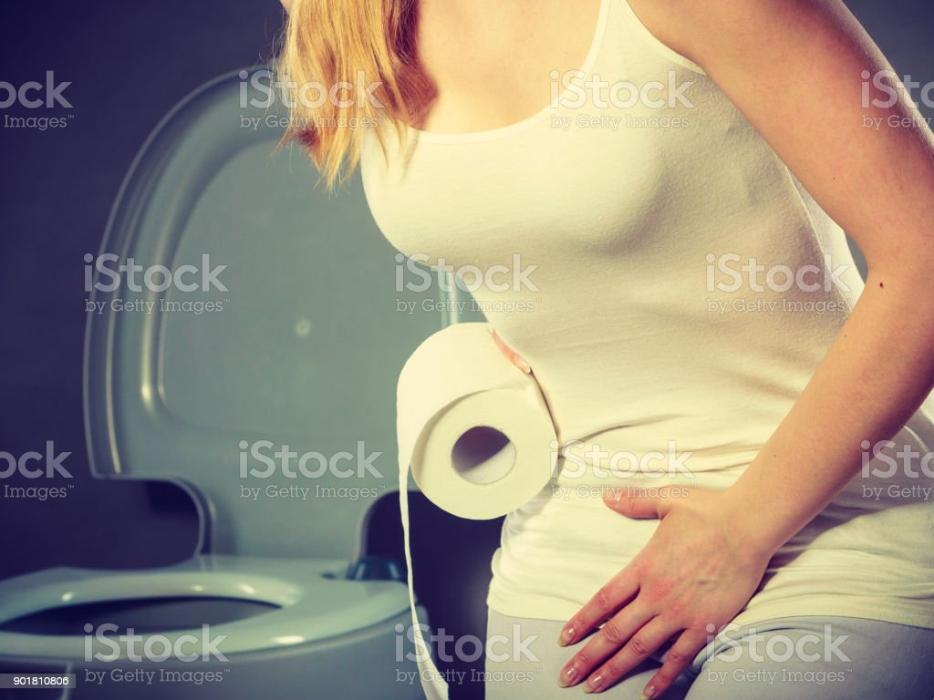 woman with hands holding her crotch in toilet stock photo