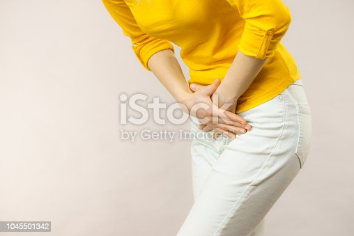Young sick woman with hands holding pressing her crotch lower abdomen. Medical or gynecological problems, healthcare concept
