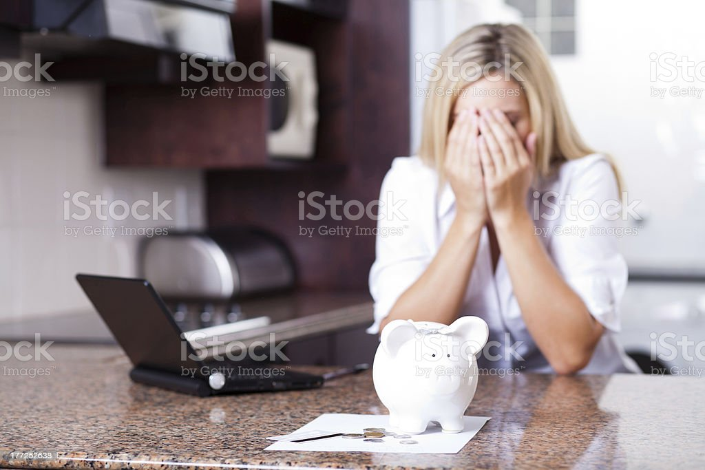 Woman with hands on face behind a laptop and piggybank - Royalty-free 20-29 Years Stock Photo