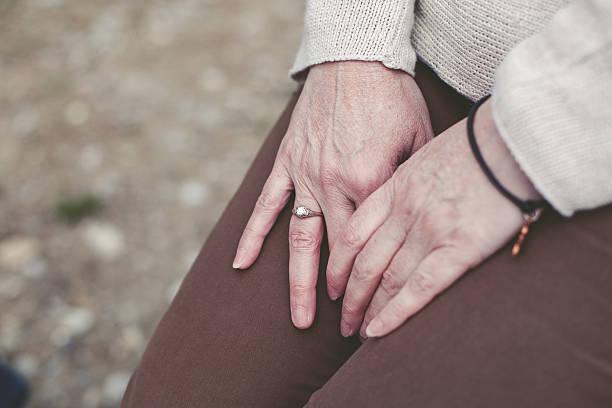 frau mit hand auf knie - canda armband stock-fotos und bilder