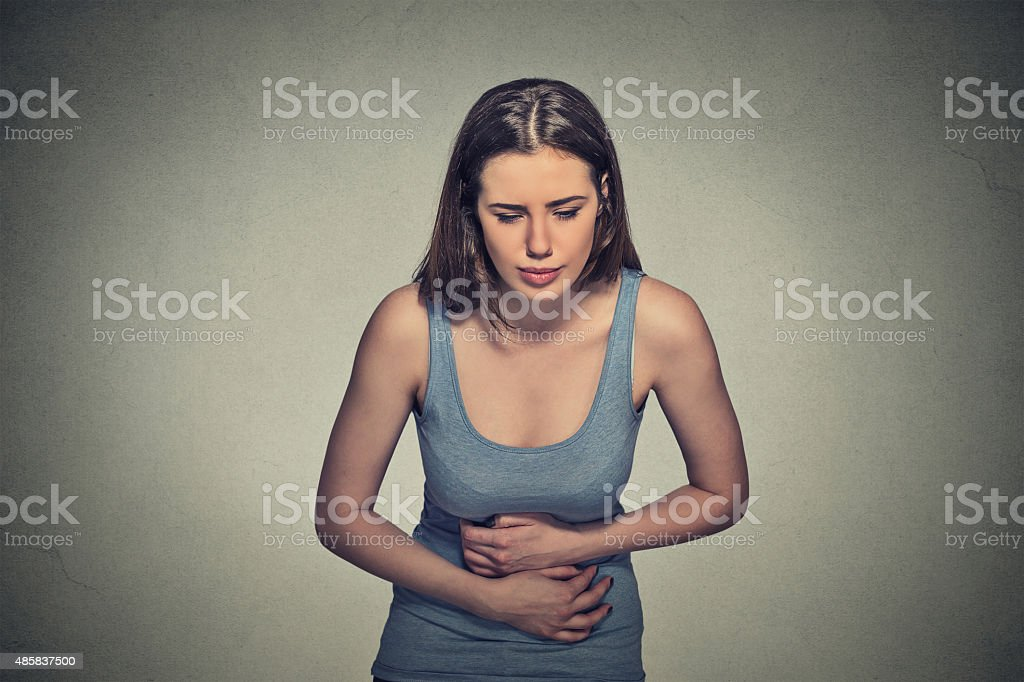 woman with hands on stomach having bad aches pain stock photo