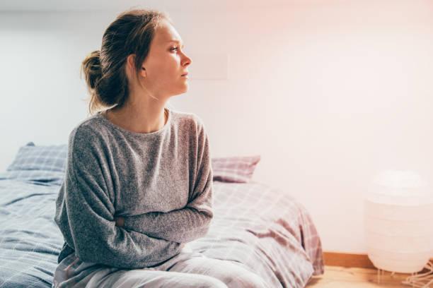 kvinna med händerna på magen lider av smärta, titta åt sidan - kronisk sjukdom bildbanksfoton och bilder