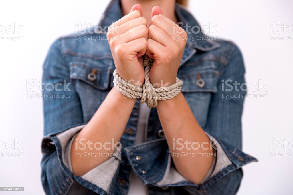 Woman with hands tied in ropes. Problems, difficulties, obstructions and limits in life. Modern slavery stock photo