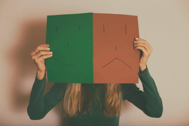 Frau mit glücklichem und traurigem Gesicht auf Papier – Foto