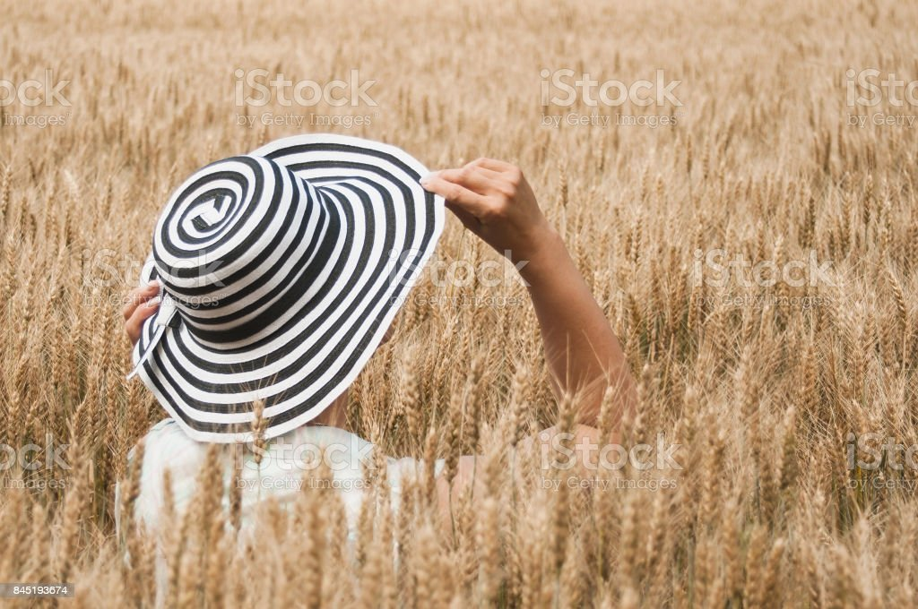 Woman with hat in a Wheat field stock photo