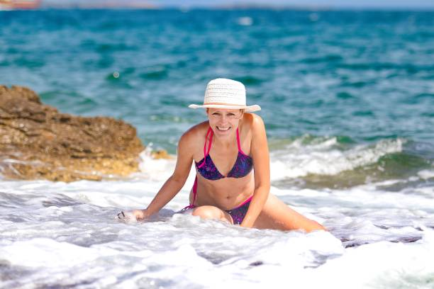 Woman with hat in the blue sea and white wave stock photo