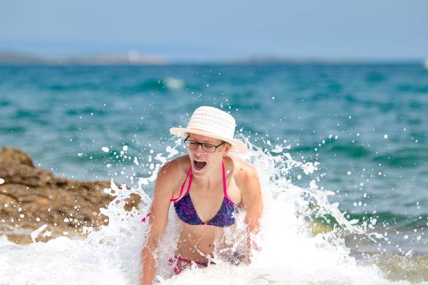 Woman with hat in the sea wave stock photo