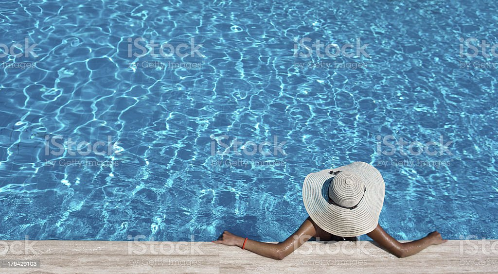 Woman with hat relaxing by the pool stock photo