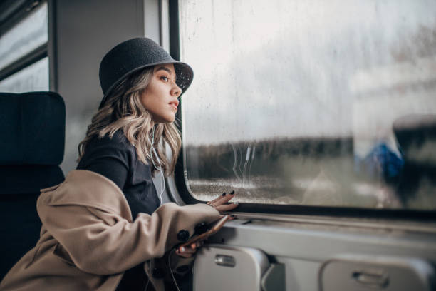 Woman with hat sitting in train stock photo