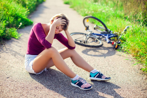 woman with head injury after biking on bicycle. sport, healthcare and people concept - head injury stock photos and pictures