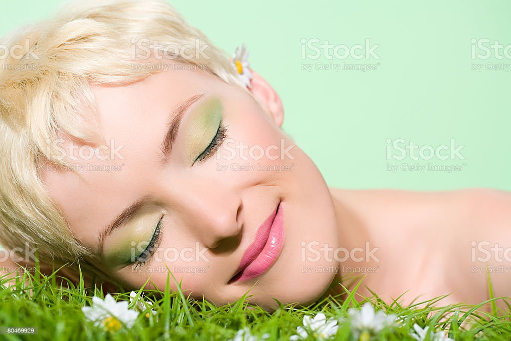 Woman with head on grass 免版稅 stock photo