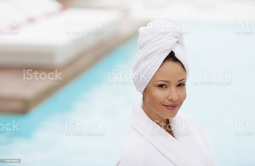 Woman with head wrapped in towel at poolside
