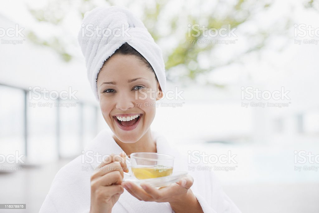 Woman with head wrapped in towel drinking tea royalty-free stock photo