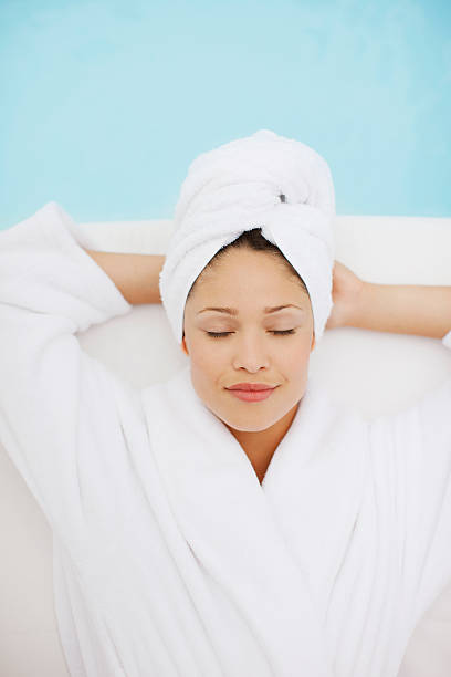 Woman with head wrapped in towel laying at poolside stock photo