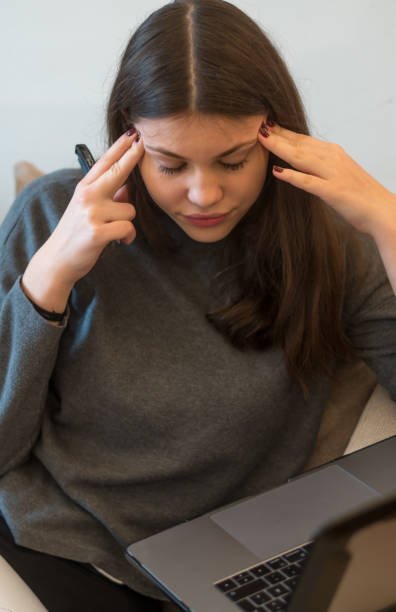Woman with headache holding her head on the laptop computer stock photo