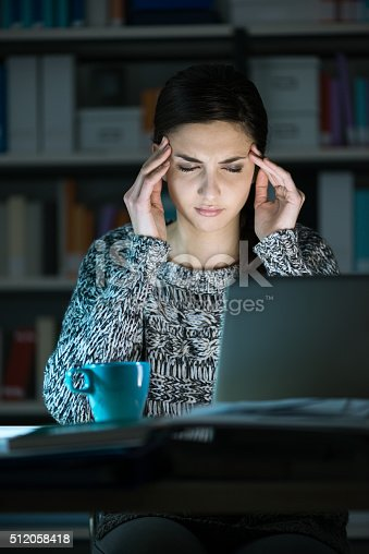 istock Woman with headache late at night 512058418