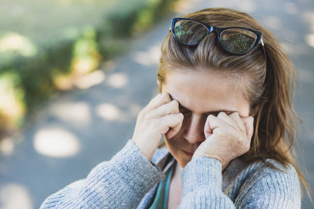 Woman with headache rubbing her eyes outside stock photo