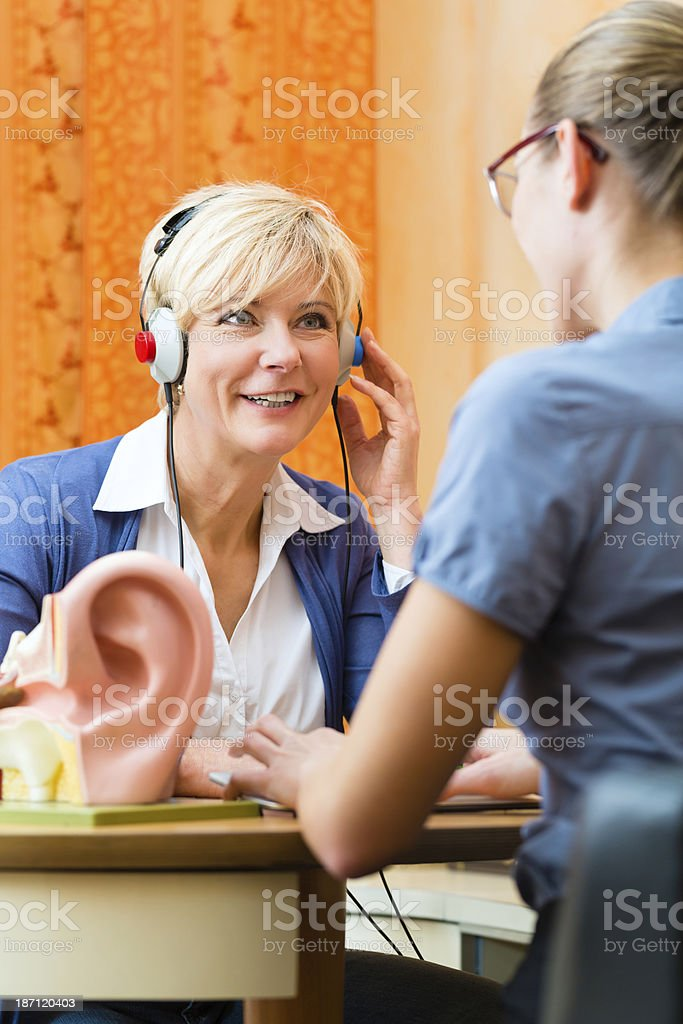 A woman with headphones is taking a hearing test stock photo